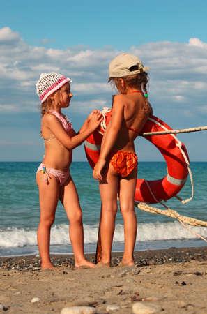 Zwei kleinen Schwestern in Badeanzügen steht auf Strand nahe Metallstange, auf der Pole hängenden roten Rettungsring Standard-Bild - 17730031