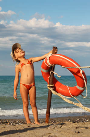 beautiful little girl in bathing suit and cap standing on beach. she clings to metal pole, on pole hanging red life buoy Standard-Bild