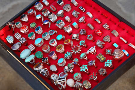 few rows of souvenir large rings on red backing. sale. wide range. bijouterie