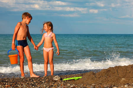 brother and sister hold hands and stand on beach. boy holding plastic orange bucket Stock Photo