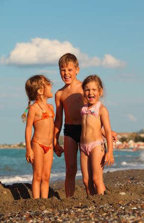 klein meisje op strand: broertje en twee zusjes staan op het strand. Kinderen schreeuwen. focus op juiste meisje Stockfoto