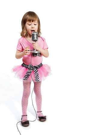 Little girl in pink with microphone sings a song. photo