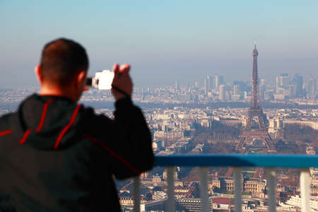 panoramic roof: PARIS - JANUARY 4: Man photographs of panorama of Paris with Eiffel Tower on January 4, 2010 in Paris, France. Eiffel Tower is highest monument in France use 20000 light bulbs in show