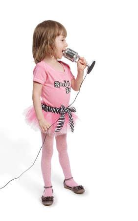 Ni�a en rosa con bases de micr�fonos en cuerpo entero se volvi� a medias y canta. photo