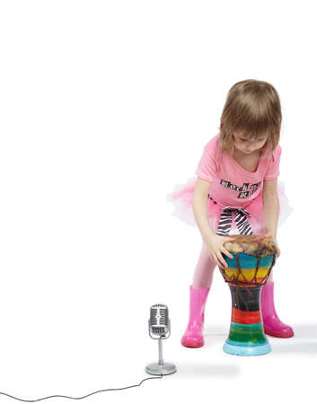 djembe: Little girl in pink going to play on the Djembe in front of a microphone.