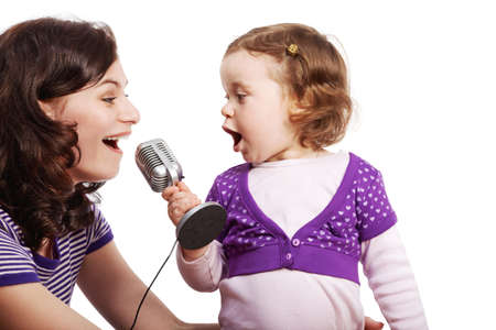 Mother and her little daughter sing into the microphone, looking at each other.