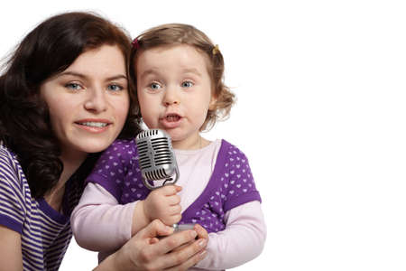 Mother hugs her little daughter, which sings into microphone. photo