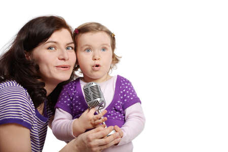 Mother with little daughter cheek to cheek sing into microphone. photo