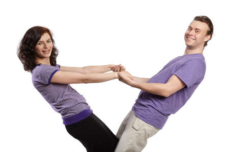 Young man and woman stand, holding each other's outstretched arms and leaning back. photo