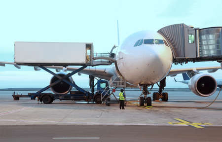 airliner parked at airport. boarding passengers. service technician