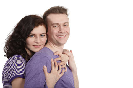 Young woman embraces a young man from behind. photo
