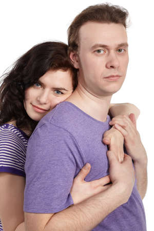Slightly smiling young woman embraces a serious young man from behind. photo