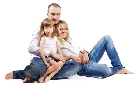 Father, mother and little daughter in white shirts and jeans sit on the floor. Stock Photo - 17730259