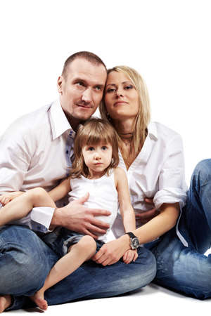 Family in white shirts and blue jeans sits on the floor. Stock Photo - 17730284