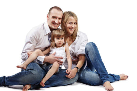 The family of three persons (father, mother and littlel daughter) in white shirts and blue jeans sits on a floor. Stock Photo - 17749827
