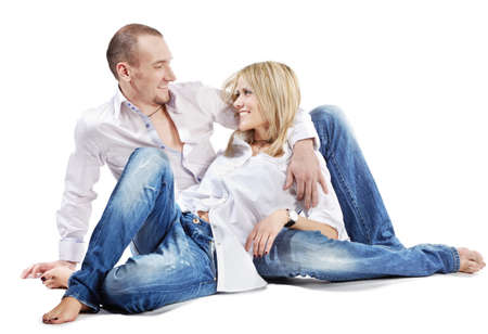 Young man and young woman in white shirts and blue jeans sit on the floor. photo