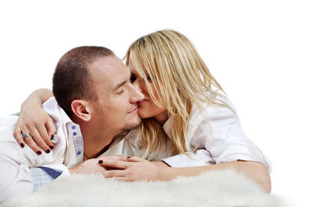 rubbing noses: The young pair in white shirts embraces and rubs  their noses, lying on a white fleecy carpet.