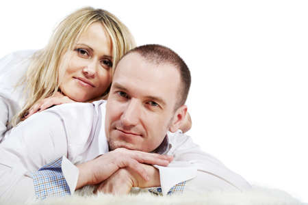 enclosing: Man  in white shirt lies on the white carpet and woman in white shirt lies on his back, enclosing hands under their heads. Stock Photo