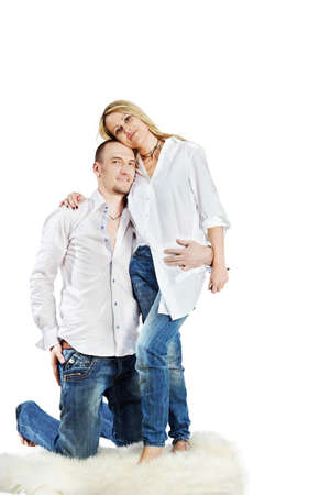 hugging knees: Man and woman in white shirts and blue jeans embrace on the white carpet, she stands in full growth, and he stands in front of her on knees.