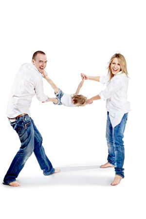 Father and mother in the white shirts and blue jeans shake the child for hands and for feet and laugh cheerfully. photo
