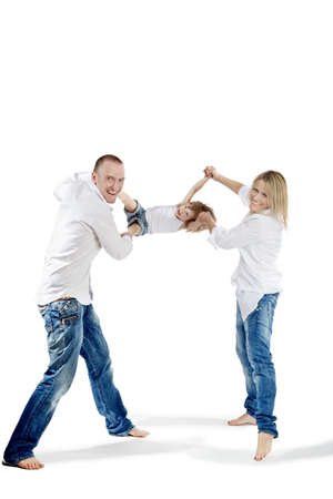 Father and mother in the white shirts and blue jeans swing their little daughter for hands and for feet, all three laugh cheerfully. photo