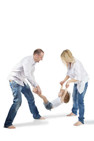 Father and mother hold their little daughter for the hands and for the feet and laugh cheerfully. photo