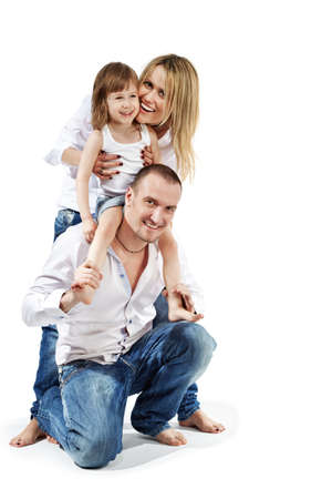 nestle: Father stands on one knee, little daughter sits on his shoulders and mother supports her from behind  nestling on her cheek. Stock Photo