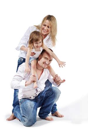 apoyo familiar: Padre se encuentra en una rodilla, la hija se sienta en los hombros y tira de las manos hacia adelante, la madre la apoya por detrás.
