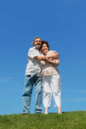 old man and woman standing on summer lawn, embracing and smiling Stock Photo - 17724294