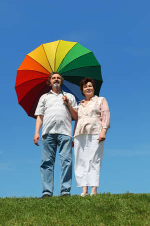 old woman and man standing on summer lawn and holding multicolored umbrella Stock Photo - 17724681
