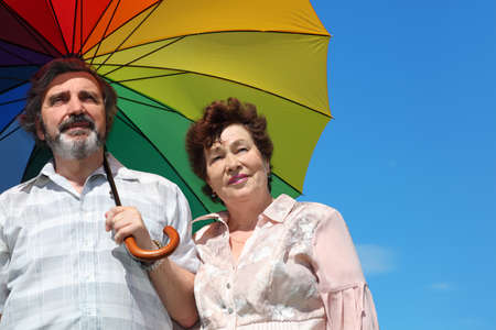 portrait of old woman and man holding multicolored umbrella photo