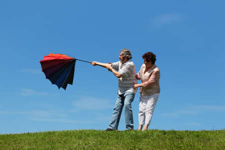 gale: old woman and man standing on summer lawn with multicolored umbrella, wind evert it Stock Photo