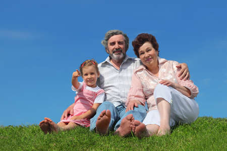 barefooted: barefooted old man and woman sitting on lawn with their granddaughter, girl pointing by finger