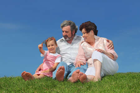 barefooted: barefooted old man and woman sitting on summer lawn with their granddaughter, girl pointing by finger Stock Photo