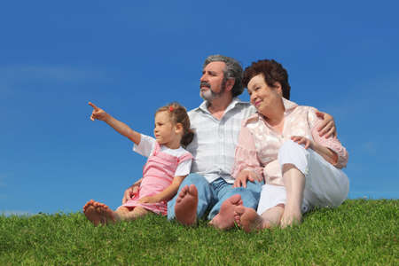 barefooted old man and woman sitting on lawn with their granddaughter, girl pointing by finger at side Stock Photo - 17724678