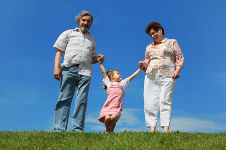 little girl and her grandparents standing on lawn and holding for hands, girl hanging Stock Photo - 17724685