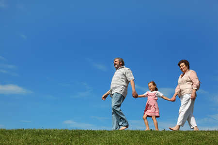 little girl and her grandparents walking on lawn and holding for hands, side view Stock Photo - 17724223