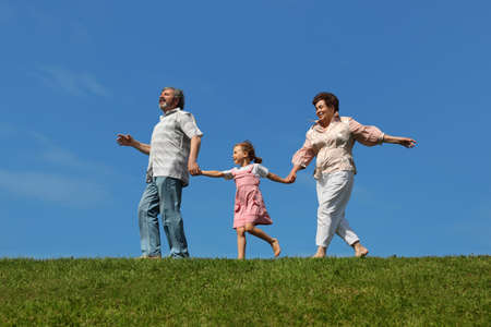 heir: little girl and her grandparents running on lawn and holding for hands, side view