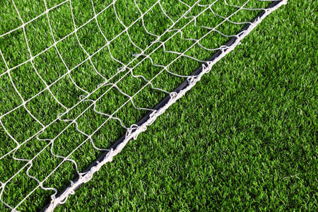 White net for football lying on green artificial grass of football field Stock Photo - 17677740