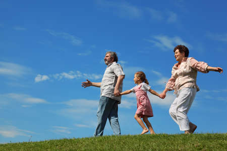 little girl and her grandparents running on hill and holding for hands, side view Stock Photo - 17724471