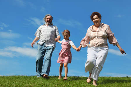 barefooted little girl and her grandparents running on summer lawn, smiling and holding for hands Stock Photo - 17724541