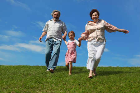 barefooted: barefooted little girl and her grandparents running on summer lawn and holding for hands Stock Photo
