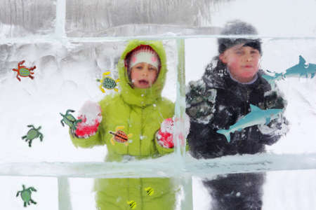 children behind ice with fish toy photo