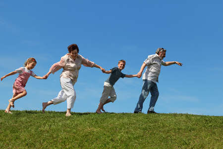 grandchildren and their grandparents running on lawn and holding for hands, side view