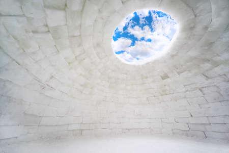 Inside empty house of ice, eskimo igloo, blue sky and clouds