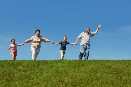 grandchildren and their grandparents running on hill and holding for hands Stock Photo - 17744500