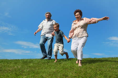 boy and her grandparents running on summer lawn and holding for hands Stock Photo - 17724575