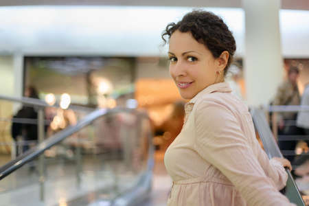 Beautiful young smiling woman standing on escalator at supermarket photo