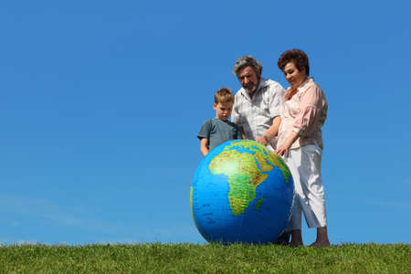 boy and his grandparents standing on lawn and looking on big inflatable globe Stock Photo - 17724475