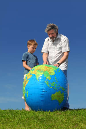 boy and his grandfather standing on lawn and looking on big inflatable globe Stock Photo - 17724553